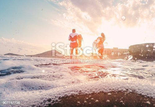 istock Surfers couple running with surf boards on the beach - Sporty people having fun in sunny day - Extreme sport, travel and vacation concept - Focus on bodies silhouettes - Water on camera lens 907747736