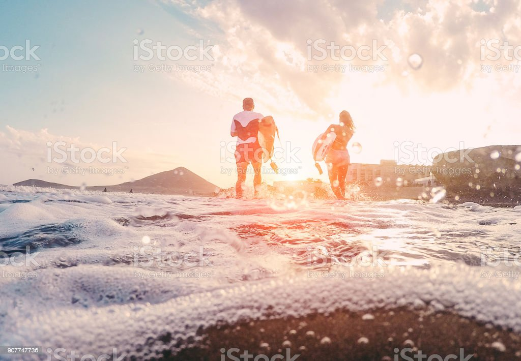 Surfers couple running with surf boards on the beach - Sporty people having fun in sunny day - Extreme sport, travel and vacation concept - Focus on bodies silhouettes - Water on camera lens stock photo