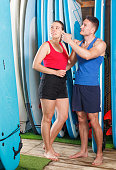 Sports guy and girl surfers discussing while choosing boards and wetsuits for rent at a shop. Focus on both persons