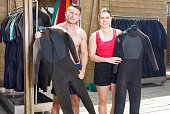 Sports guy and girl surfers discussing while choosing the boards and wetsuits for rent at a shop. Focus on both persons