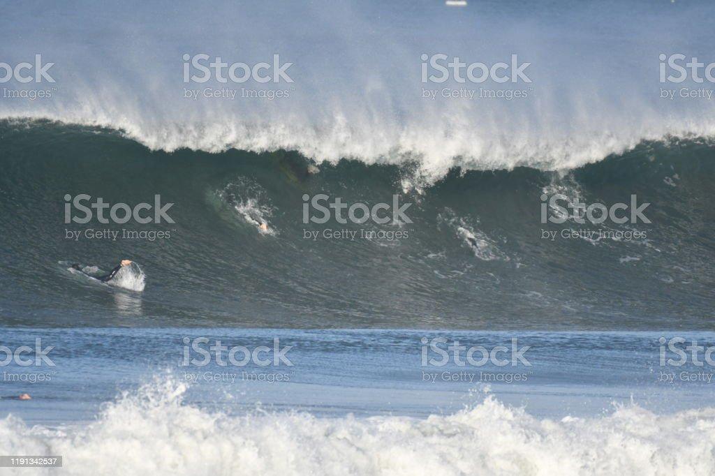 Surfers Diving under large wave Los Angeles Area Surf break Horizontal Stock Photo