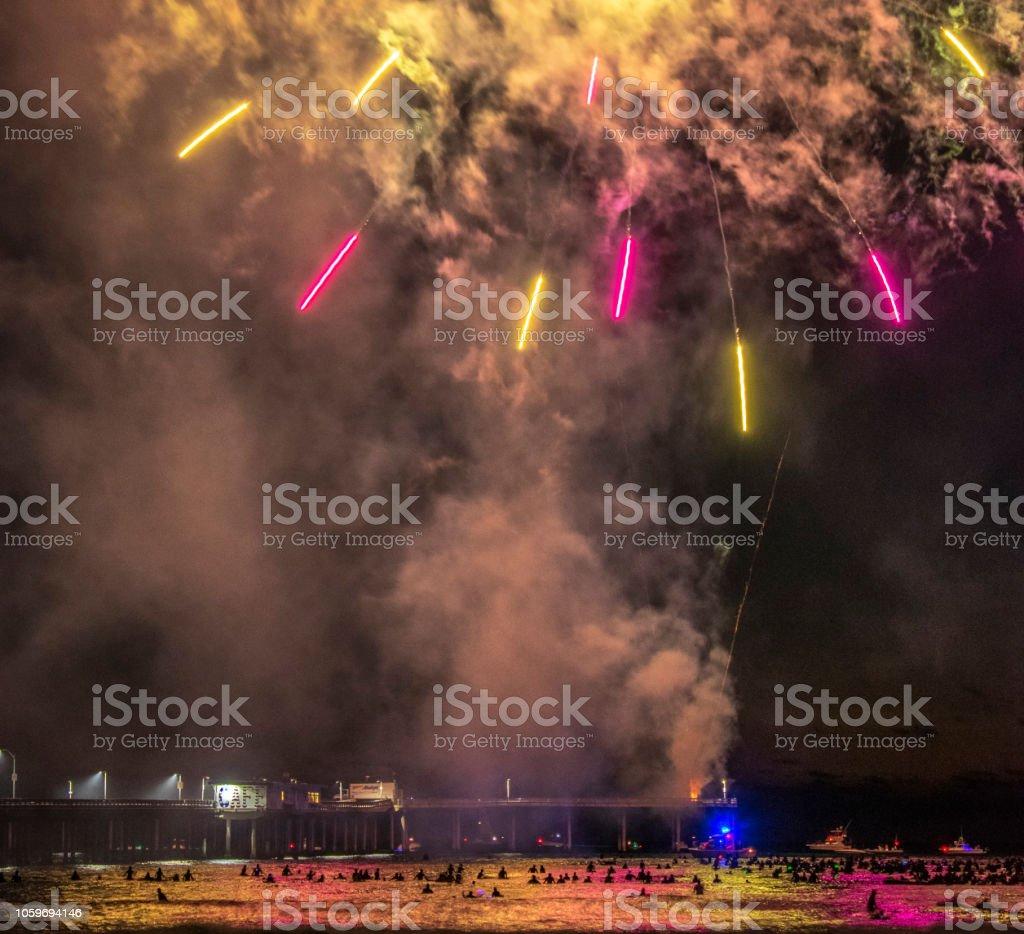Surfers enjoying the Fireworks of 4th of July, Ocean Beach, San Diego, California. stock photo