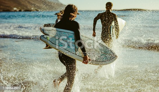 Rear view of two men going in to the sea with surfboards. Male surfers running into ocean water for surfing.