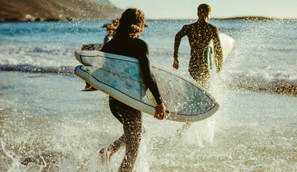 Surfers going for water surfing stock photo