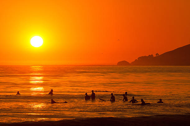 Surfers Paddle Out at Sunset stock photo
