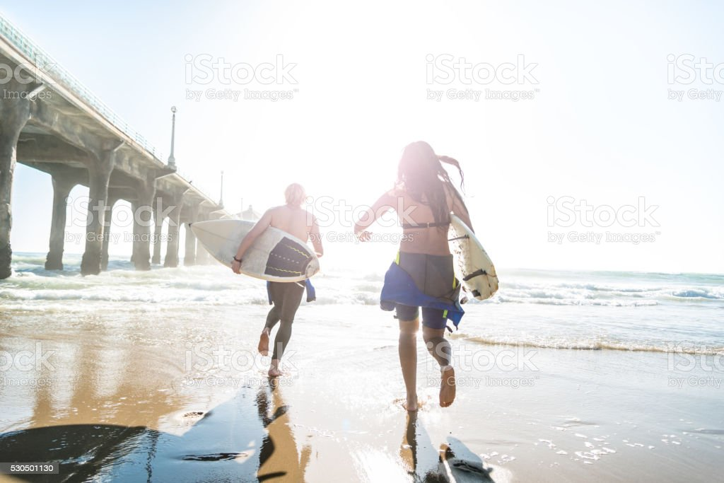 surfers running on the beach entering on the water stock photo