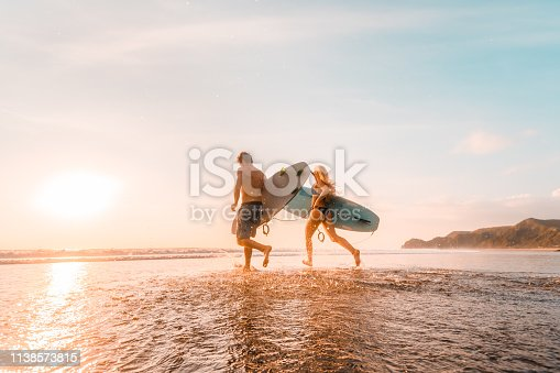 Young couple with their surfboards heading to Piha beach, for surfing.