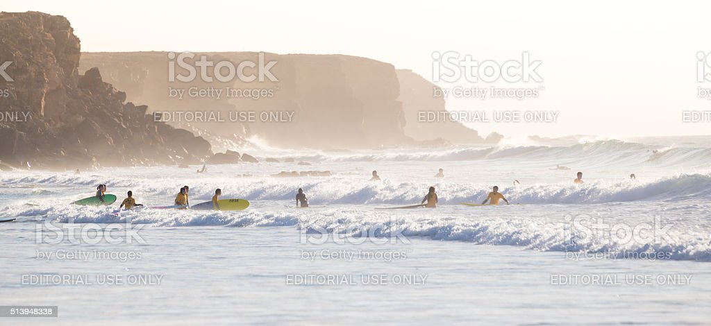 Surfers surfing on El Cotillo beach, Fuerteventura, Canary Islands, Spain. stock photo