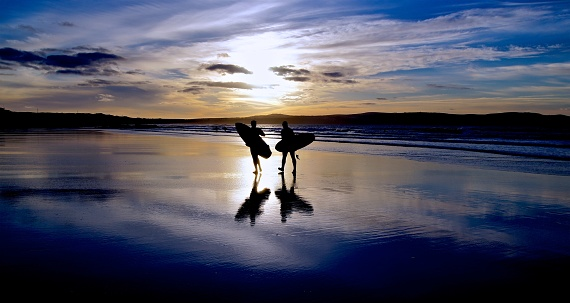 Surfers walking across a beach at sunset in St Ives Bay Cornwall