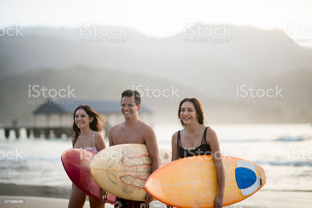 Surfers Walking on the Beach stock photo
