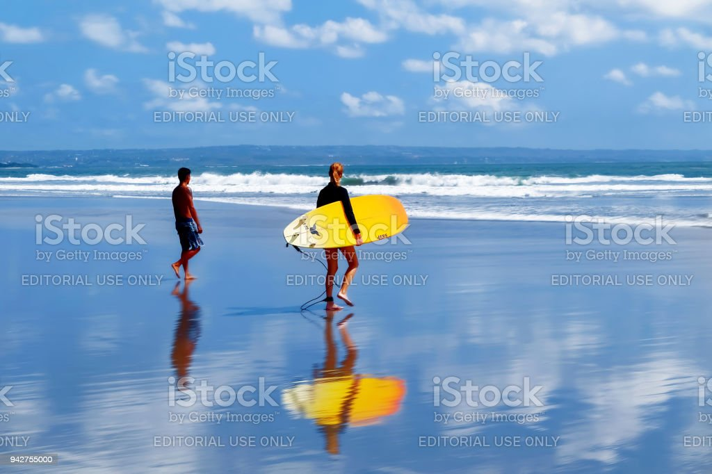 Surfers with a surfboard walking along the beach. School of surfing in Bali. Colored reflections in the water. stock photo