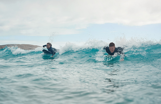 Shot of a young couple out surfing together at the beach