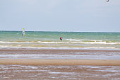 Surfing and kites surfers in North Sea Belgium in summer. Scene is near De Panne