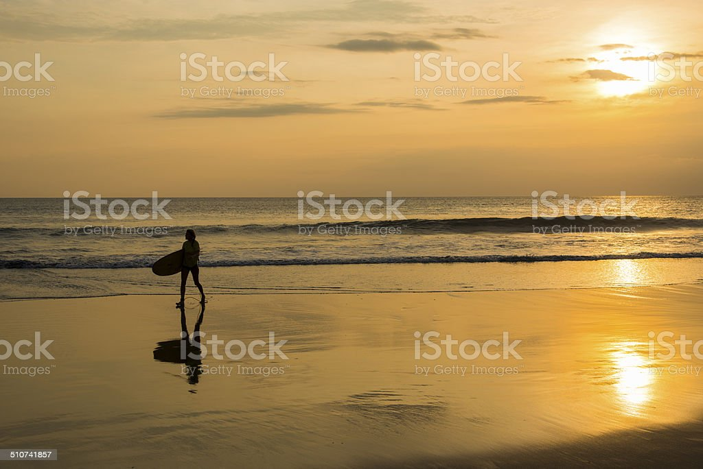 Surfing at sunset, End of Perfect Day in paradise stock photo