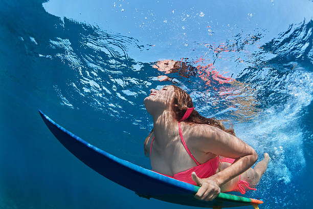 Surfing girl with board dive under ocean wave stock photo