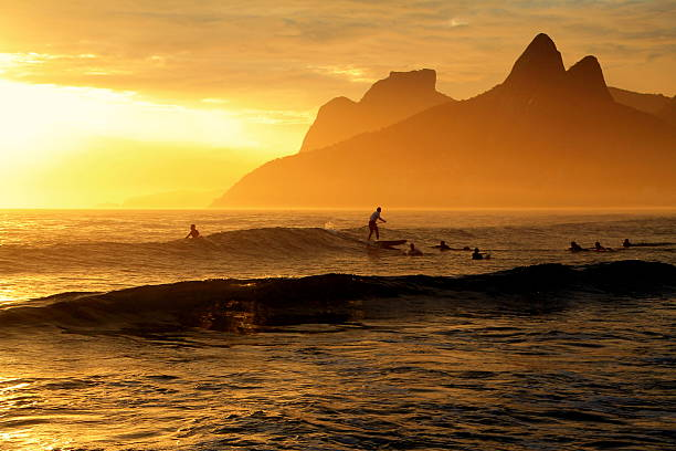Surfing in a beautiful sunset in Ipanema Beach stock photo