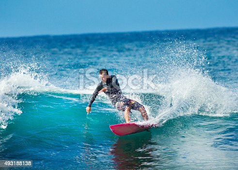 A young native Hawaii man surfing on the wave of Poipu Beach, on the island of Kauai, Hawaii, USA. He is on a pink surfboard and riding the wave in high speed in the aqua sea of Kauai. Photographed in horizontal format with copy space available.
