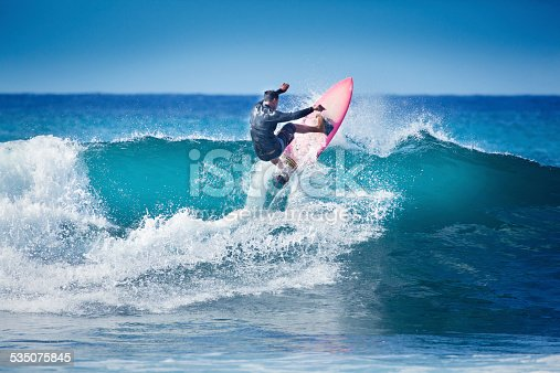Young surfer surfing the wave of Kauai, Hawaii, USA.