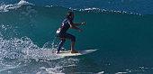 Playa De Las Americas, Tenerife, Spain. – January 23, 2016: A male surfer rides a wave at the beach in Las Americas, Tenerife, Spain.