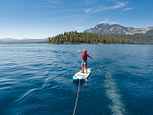 A family camps and enjoys the beauty of Emerald Bay in Lake Tahoe, California while paddle boarding, sailing, and swimming