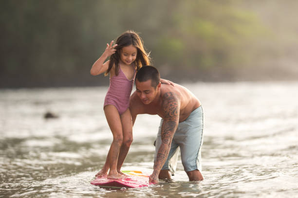surfing lesson - hawaiian ethnicity stock photos and pictures