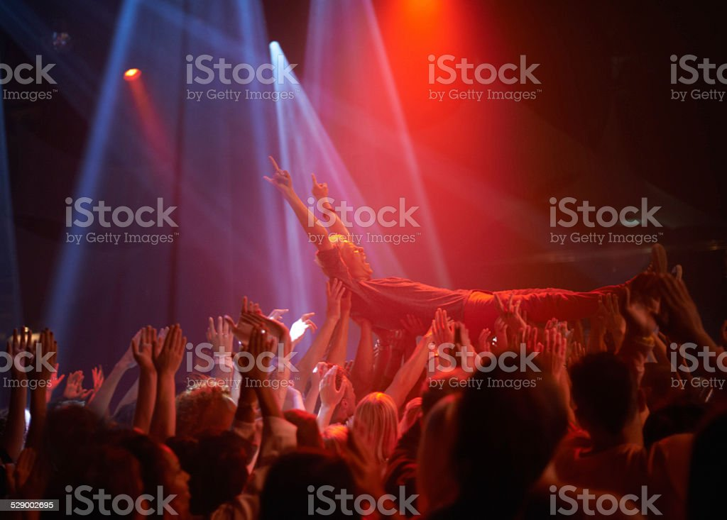 Surfing on a crowd of fans stock photo