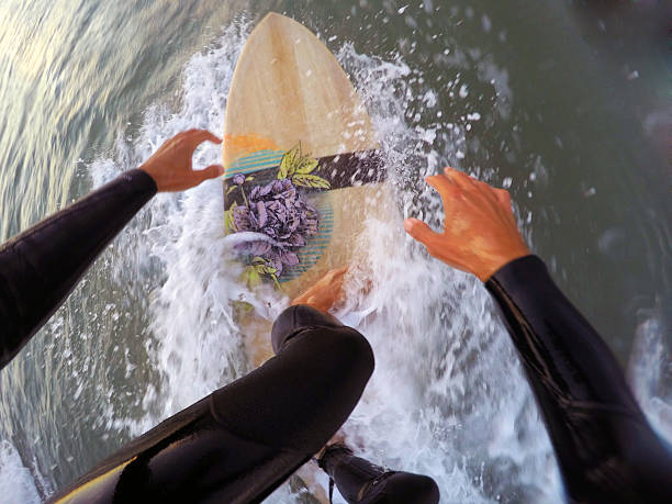 Surfing on a wooden surfboard (point of view) stock photo