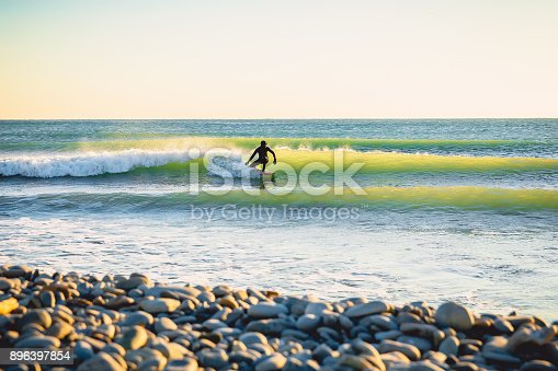 Surfing on ocean wave at sunset or sunrise. Winter surfing in wetsuit