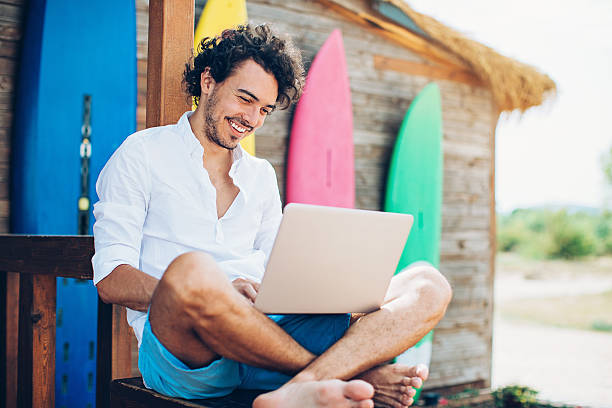 Surfing Cheerful young man using laptop with surfing boards at the background. beach hut stock pictures, royalty-free photos & images