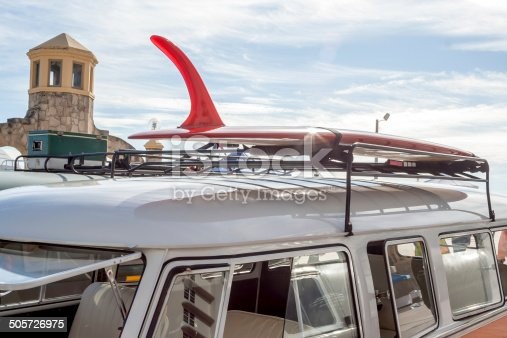 A surfboard and an old retro cooler loaded on the roof racks of two old camper vans on a road trip to Daytona Beach Florida. A cool lens flare gleams off the surfboard in the morning sunlight.