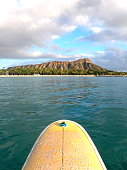 Canoes and populars surfbreak in Waikiki with a perfect view on the gigantic crater and the Diamond Head on a rather cloudy day.