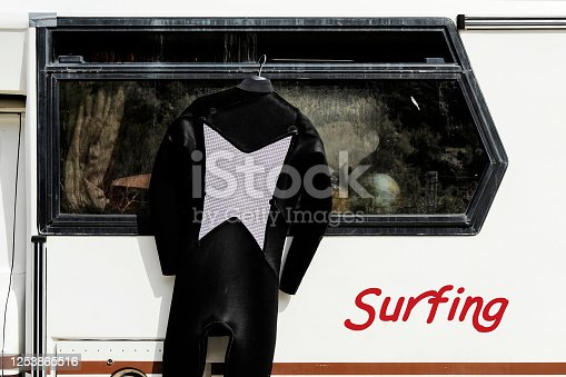 Surfing suit hanging on the side of a vintage caravan - Camper of surfer with a surfing suit on clothes hanger for drying outdoors - Nomadic life concept of surfer waiting for better waves - Surfing