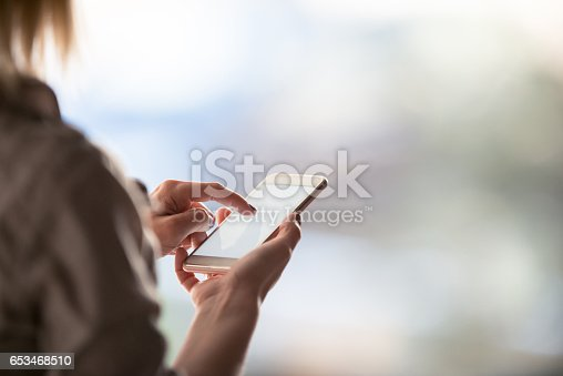 Close up of a woman using smart phone.