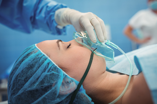 Surgeon Adjusting Oxygen Mask On Patient Mouth In Operation Theater Stock Photo - Download Image Now