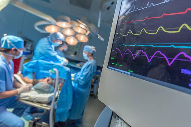 surgeon and patient in operating theatre - ventilator bed stockfoto's en -beelden