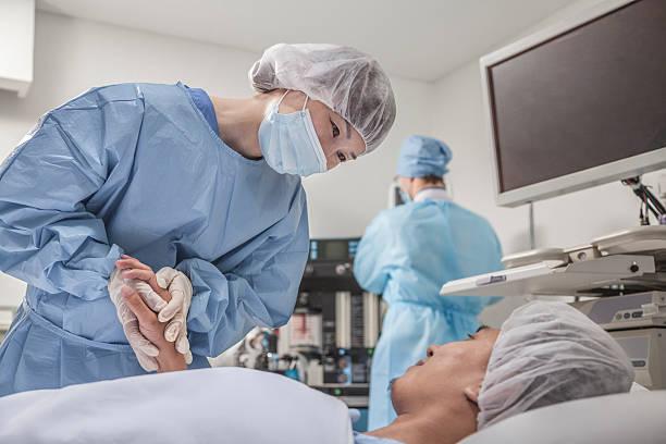 cirurgião consultar um paciente, segurando as mãos, preparando-se para a cirurgia - cirurgião - fotografias e filmes do acervo