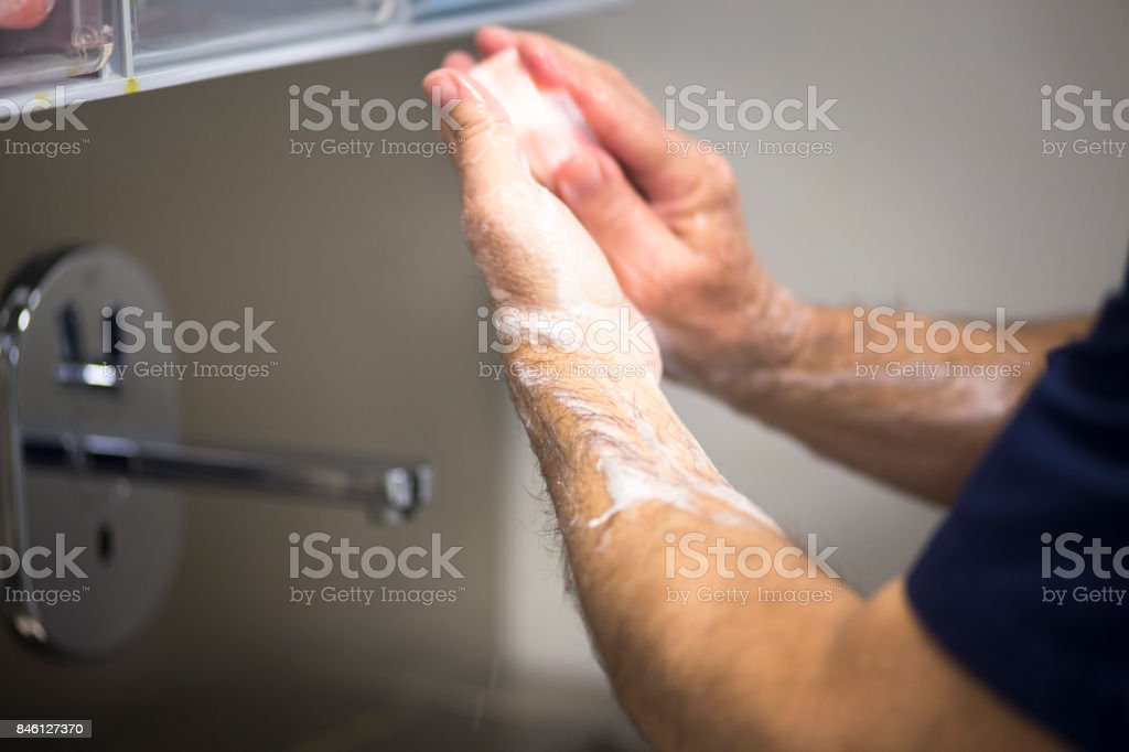 Surgeon in hospital surgery washing handsin sterile uniform 'scrubs' before operating theater emergency room. stock photo