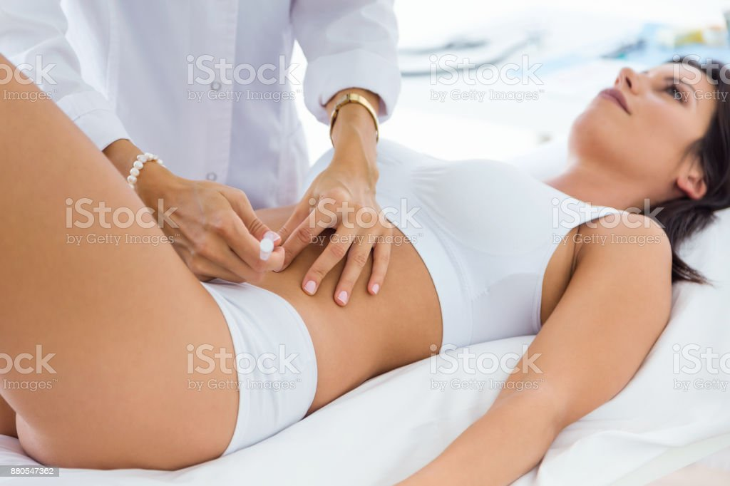 Surgeon making injection into female body. Liposuction concept. stock photo