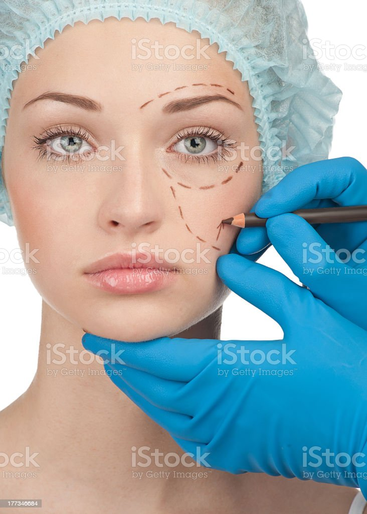 Surgeon marking up a female for plastic surgery royalty-free stock photo
