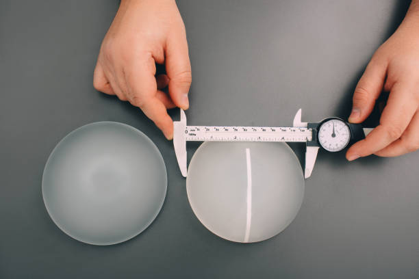 Surgeon measure size silicone breast implants, close-up, view from above. Surgeon measure size silicone breast implants, close-up, view from above. Cosmetic breast surgery. silicon stock pictures, royalty-free photos & images