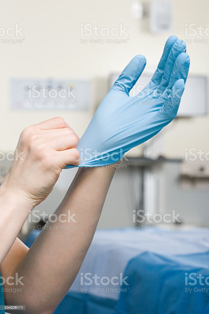 Surgeon putting on glove stock photo