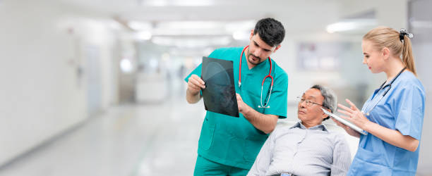 Surgeon showing xray film to senior patient looking at brain injuries with nurse standing beside the surgeon at the hospital room. Medical healthcare and surgical doctor service concept. Surgeon showing xray film to senior patient looking at brain injuries with nurse standing beside the surgeon at the hospital room. Medical healthcare and surgical doctor service concept. inpatient stock pictures, royalty-free photos & images