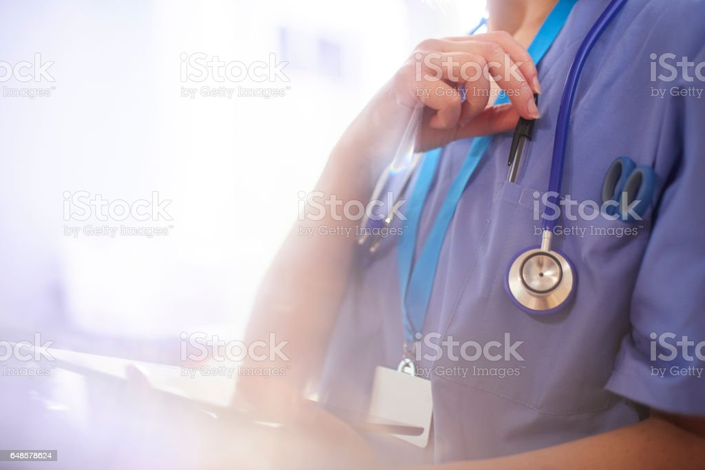 Surgeon using digital tablet in hospital and reaching for her pen stock photo
