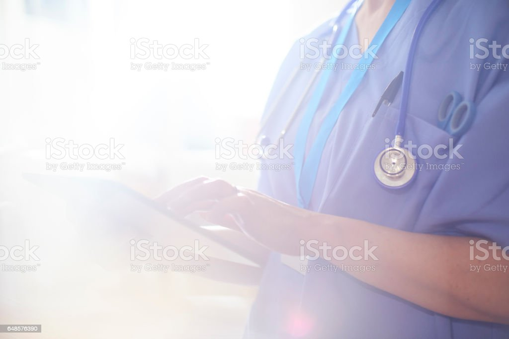 Surgeon using digital tablet in hospital stock photo