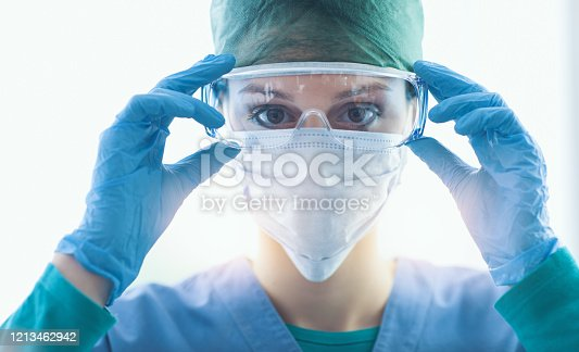 Female surgeon preparing for the surgical operation and wearing protective glasses, healthcare and safety concept