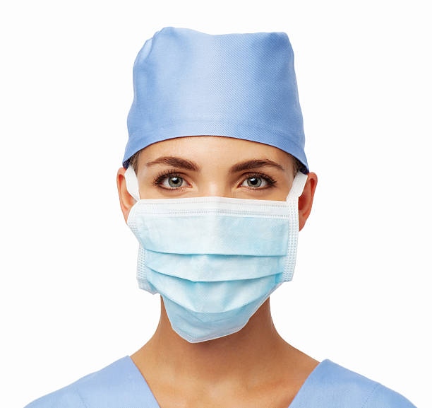Surgeon Wearing Surgical Mask And Cap Portrait of female surgeon wearing surgical mask and cap against white background. Horizontal shot. surgical cap stock pictures, royalty-free photos & images