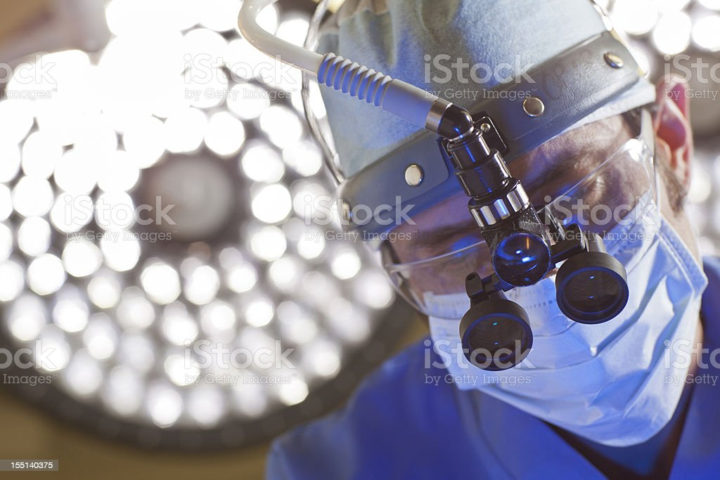 Surgeon with magnified glasses stock photo