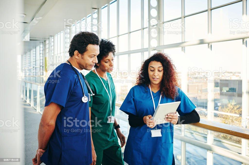 Chirurgen diskutieren über digital-Tablette im Krankenhausflur – Foto