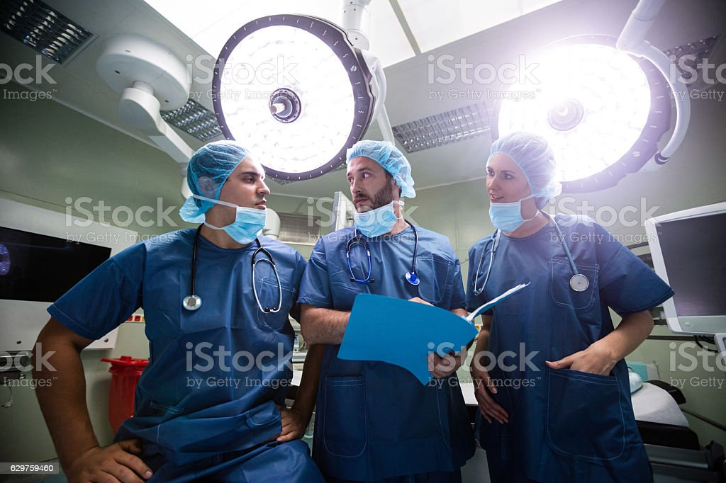 Surgeons discussing patient records in operation room stock photo