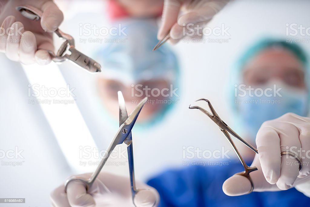 surgeons holding medical instruments in hands and looking at pat stock photo